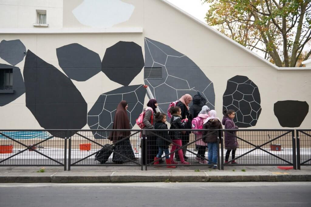Schoolkids gather in front of the mural on the side of their school